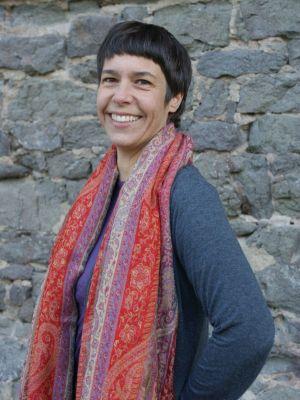 Yogalehrerin und Gründerin von Yoga Grün Darmstadt vor einer Natursteinmauer